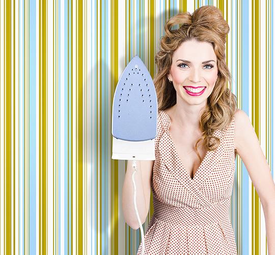 Happy retro housewife holding iron